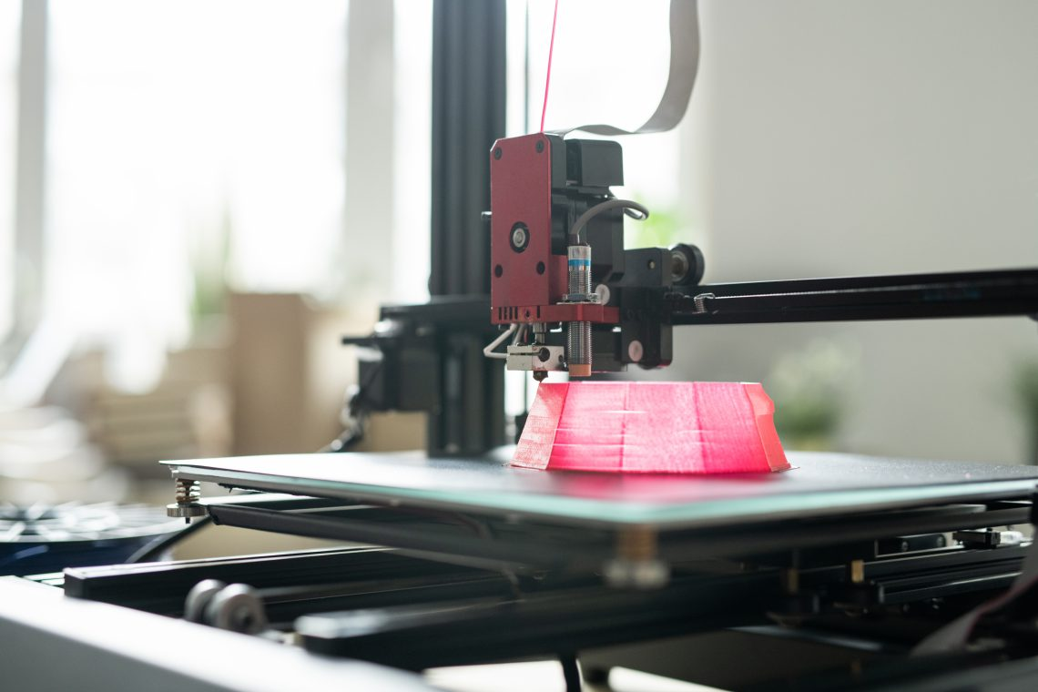 Printhead of 3d printer moving over foundation of pink round object on working layer during process of printing