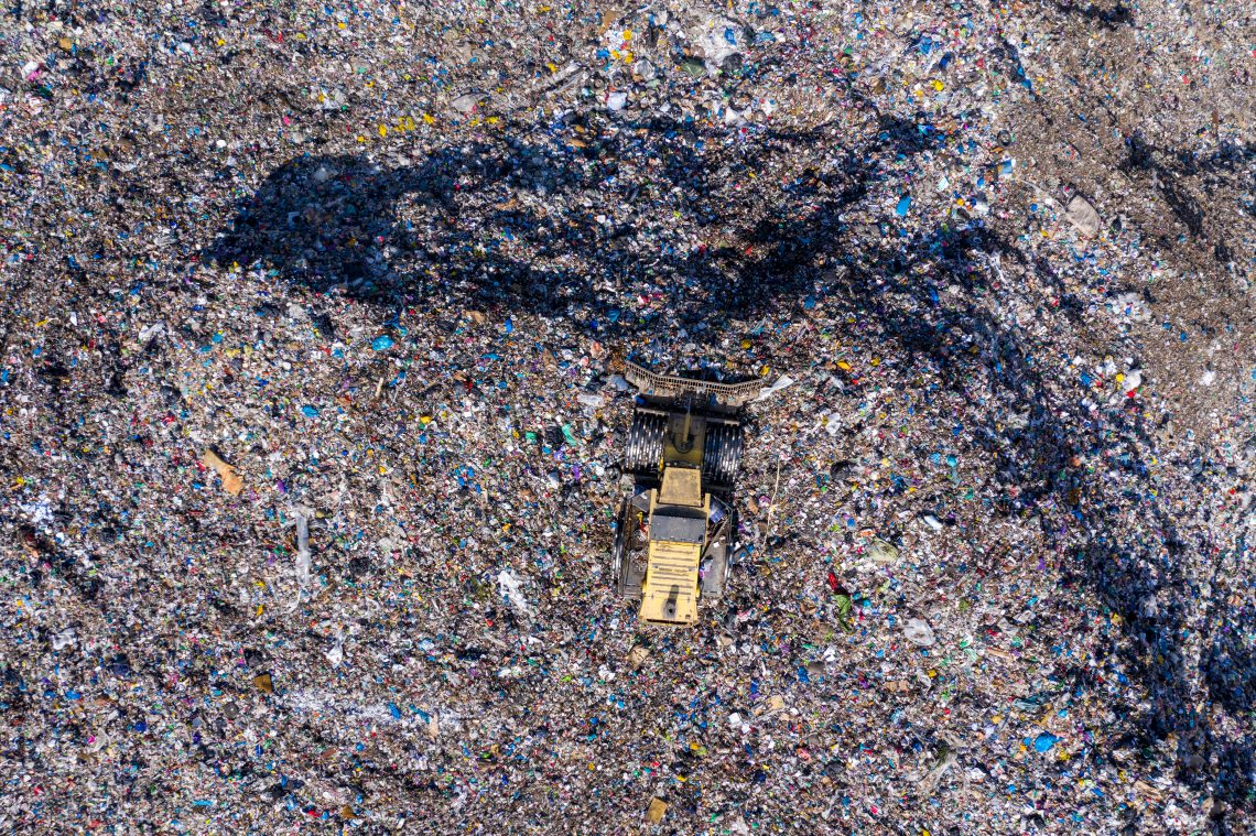 Aerial top drone view of large garbage pile, trash dump, landfill, waste from household dumping site, excavator machine is working on a mountain of garbage.