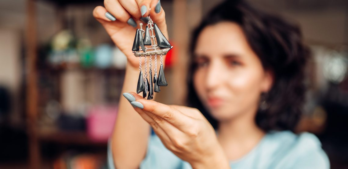 Person making handmade earrings. Needlework, bijouterie making