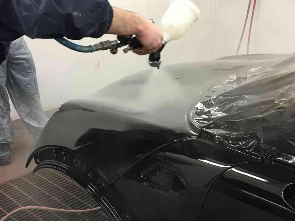 Spray painting clear coat onto car body shell